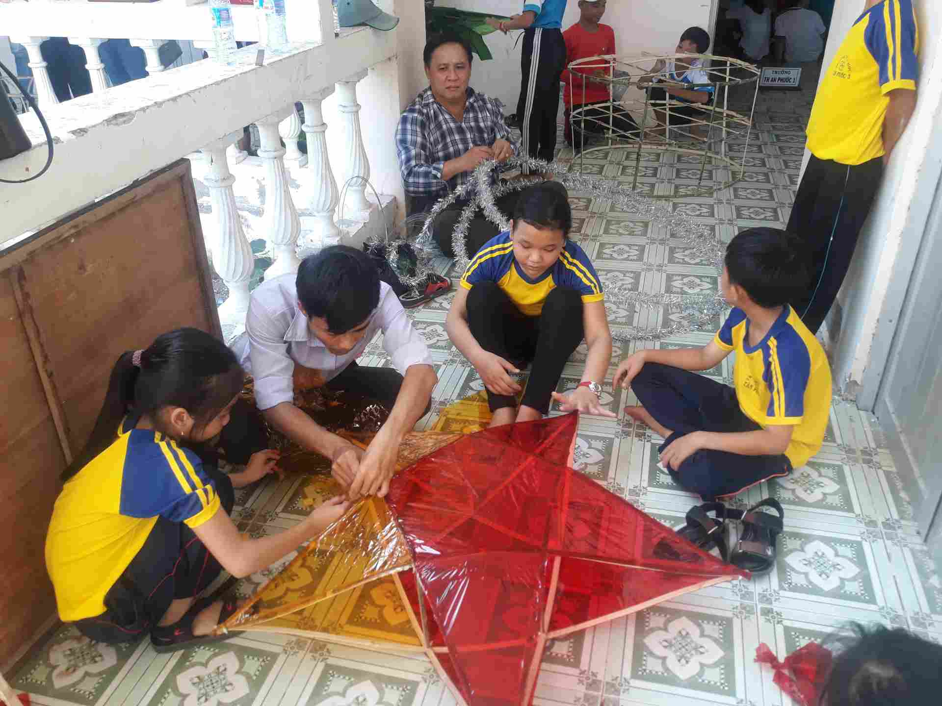 Thầy Phạm Văn Tráng và Thầy Nguyễn Văn Sang hướng dẫn các em cách làm lồng đèn